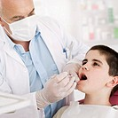 Close-up of a male dentist treating a boy (10-12)