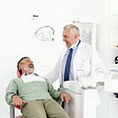 an elderly male dentist laughing with his male patient
