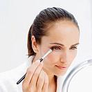 woman applying eye makeup with brush