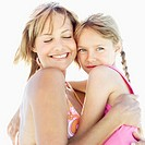 portrait of a mother and daughter (6-7) hugging each other