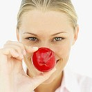 close-up of a woman holding a plum to her face