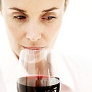 portrait of a woman sniffing a glass of red wine