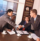 portrait of business associates shaking hands at a meeting