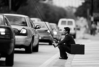 black and white side profile of a businessman sitting on a sidewalk holding a fishing rod