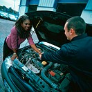 Woman shaking hands with a car salesman over a car engine