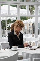 Businesswoman sitting in a cafe and using a mobile phone