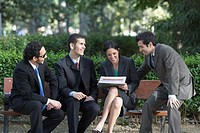 Business executives having a meeting on a park bench