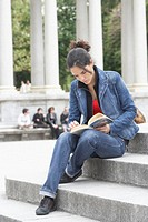 Young woman sitting on steps and reading
