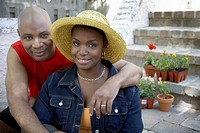 Couple sitting on steps of home, smiling, portrait, close-up