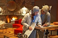 Young man and woman with skis and snowboard looking at map in lodge