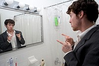 Young man pointing at reflection in mirror, side view, close-up