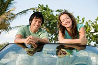 Man and woman sitting in convertible car, smiling, portrait
