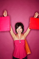Young woman against pink background holding up shopping bags