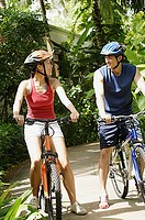 Couple on bicycles, smiling at each other