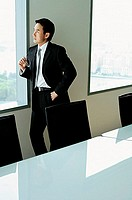 Businessman standing next to window in conference room
