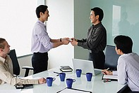 Executives in meeting room, exchanging business cards