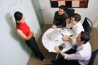 Executives in meeting room, female executive standing, talking