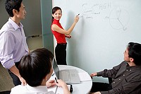 Executives in meeting room, female executive writing on white board