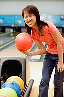 Woman at bowling alley with bowling ball, smiling at camera