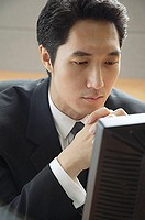 Businessman sitting at desk, looking at computer monitor