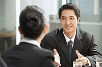 Businessman having discussion with businesswoman, over the shoulder view
