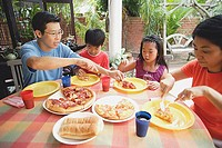 Family of four having pizza on patio