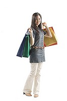 Young woman standing with shopping bags, looking at camera