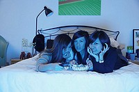 Three girls in bedroom, lying on bed, watching TV
