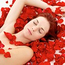 high angle view of a naked young woman covered with rose petals