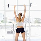 rear view of a young woman lifting a barbell