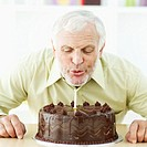 Close-up of an elderly man blowing out a candle on a birthday cake