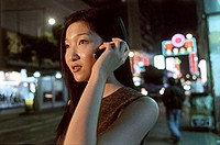 Female executive talking on cellular phone with neon in background