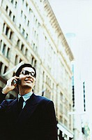 Male executive wearing sunglasses using cellular phone, building in background ( high grain)
