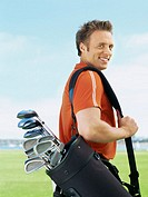 side profile of a young man carrying a golf bag