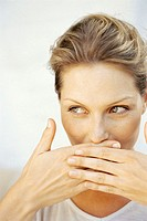 close-up of a young woman covering her mouth with her hands