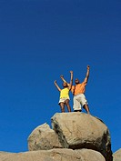 low angle view of a young man and a young woman standing on a rock with their hands raised
