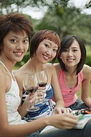 Young women sitting, looking at camera, wine glasses in hand
