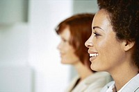 side profile of two businesswomen smiling in an office