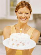 portrait of a young woman holding a birthday cake