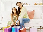 mother sitting with her daughter holding shopping bags