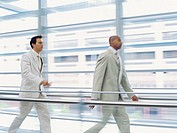 side profile of two businessmen walking in an office