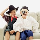 portrait of two boys dressed as a pirate and a cowboy sitting on a sofa