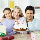 portrait of parents standing with their daughter in front of a birthday cake