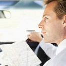 side profile of a businessman holding a map in a car