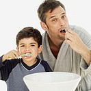 portrait of a father and his son brushing their teeth