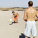 two young men playing paddle ball on the beach