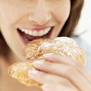 close-up of a young woman eating a croissant