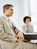 businessman and a businesswoman sitting in a conference room