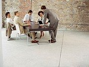 four businessmen and a businesswoman discussing in a meeting