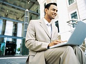 businessman sitting on stairs and using a laptop